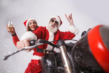 Santa Claus with white beard wearing sungasses and young mrs. Claus wearing Santa hat, red sweater and sunglasses Mrs. Claus holding champagne and Santa Claus showing a rock gesture, while riding a