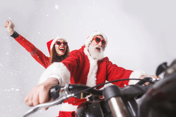 Santa Claus with white beard wearing sungasses and young mrs. Claus wearing Santa hat, red sweater and sunglasses rejoicing in the snow while riding a motorcycle when snowing, New Year, Christmas