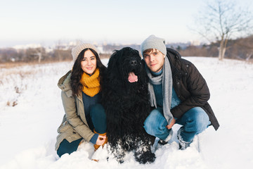 A couple enjoying winter while walking their big black dog