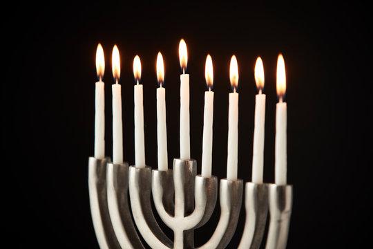 Lit Candles On Metal Hanukkah Menorah Against Black Studio Background
