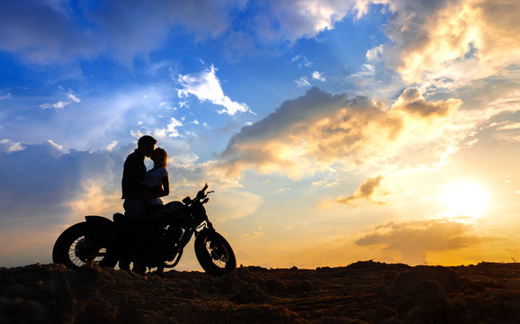 Couple in love silhouettes with motorbike  at sunset sky