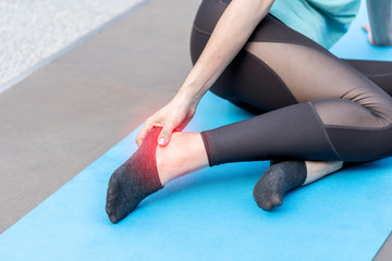 image of woman or Athlete suffering from foot pain or podalgia or ankle sprain and massaging her painful ankle having painful feet and stretching muscles fatigue to relieve pain after exercise.