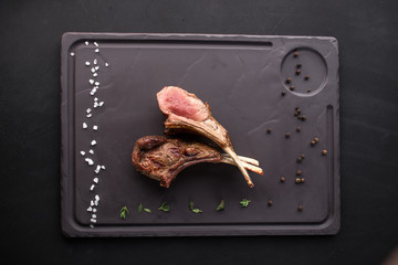 Lamb rib chops grilled on stone board on black background
