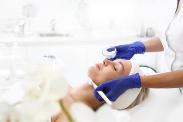 Maseczka kosmetyczna.  Kobieta w salonie kosmetycznym, kosmetyczka nakłada pędzelkiem maseczkę na skórę twarzy.