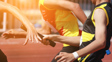 Professional Athlete passing a baton to the partner against race on racetrack.selective focus. Wall mural