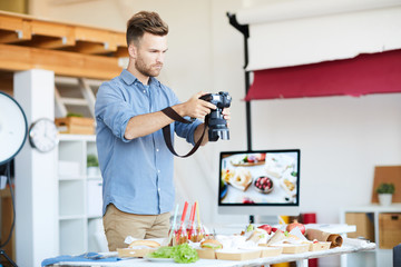 Portrait of handsome photographer taking photos of food while working in studio, copy space