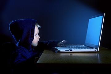 A little boy in a black hood uses a laptop in the dark.