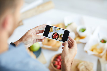 Close up of unrecognizable man taking pictures of food using smartphone, copy space