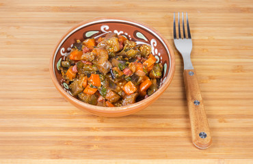 Braised chopped eggplants with other vegetables in bowl and fork