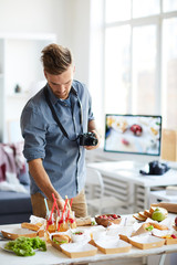 Waist up portrait of smiling photographer taking pictures of party table with food