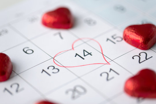 valentines day and holidays concept - close up of calendar sheet with marked 14th february date and red heart shaped chocolate candies