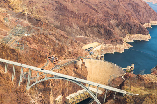 landscape and infrastructure and concept - aerial view of mike callaghan-pat tillman memorial bridge over colorado river and hoover dam at grand canyon from helicopter