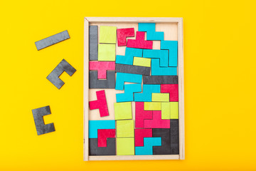 Tangram game  wooden and colorful on yellow background. Flat lay