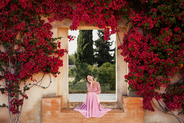 Elegant Asian lady sitting in arch near beautiful flowers