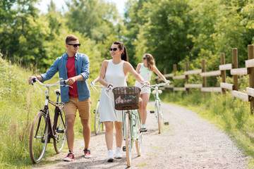 people, leisure and lifestyle concept - happy young friends with fixed gear bicycles on road in summer