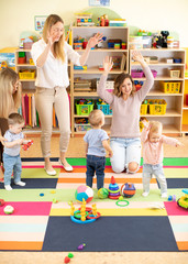 family, childhood, activity and creativity concept - happy mothers and their little kids having a fun in playroom