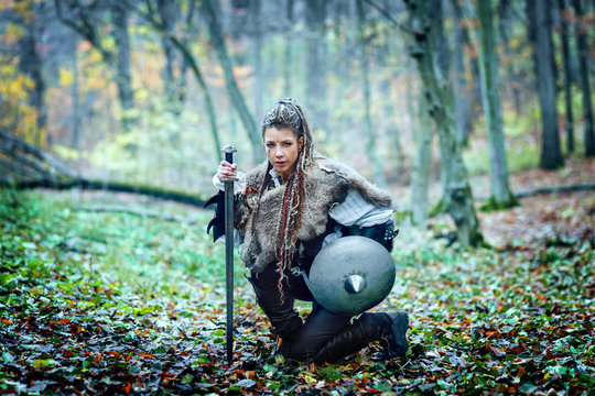 Warrior woman with braided hair and painted face holding sword and shield in forest ready to attack