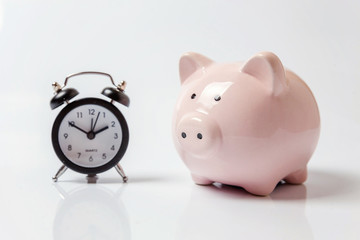 Pink piggy bank and classic alarm clock isolated on white background. Saving time investment budget wealth business retirement, financial, money, banking concept. Copy space