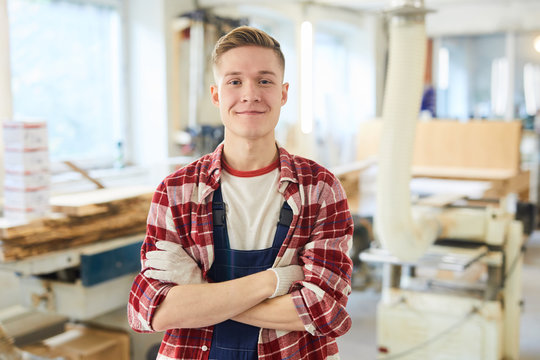 Content confident handsome young carpentry student in work gloves wearing red checkered shirt and overall standing in modern workshop and looking at camera