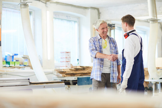 Jolly confident carpentry workers standing in modern woodworking studio and shaking hands while starting partnership