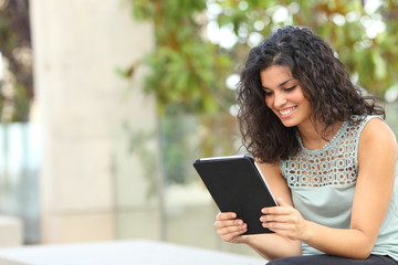 Happy woman reading online content in a tablet or ebook