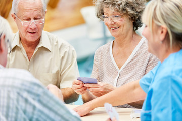 Senioren und Pflegehilfe beim Kartenspiel