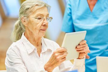 Alte Frau lernt konzentriert mit dem Tablet