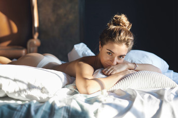 Picture of sensual gorgeous European female with beautiful slim body relaxing topless in her bedroom, lying on stomach, resting head on folded arms and staring at camera with mysterious smile