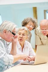 Senioren lernen zusammen am Laptop PC
