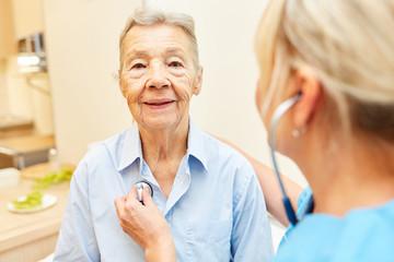 Krankenschwester hört Seniorin ab