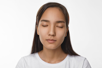 Peace, calmness, harmony and meditation concept. Beautiful young Asian woman with loose black hair having peaceful serene facial expression while meditating in studio, keeping her eyes closed