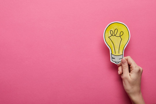 top view of hand holding yellow light bulb on pink background