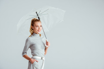 beautiful woman in grey clothes and hand in pocket posing with transparent umbrella isolated on grey