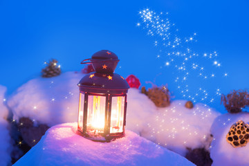 lantern with candle on snow christmas background