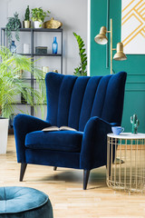 Big comfortable blue armchair next to stylish coffee table