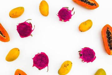 Food frame of papaya, mango and dragon fruits on white background. Flat lay. Top view. Tropical fruit concept