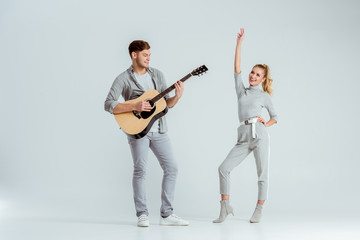 handsome man playing acoustic guitar while woman dancing on grey background
