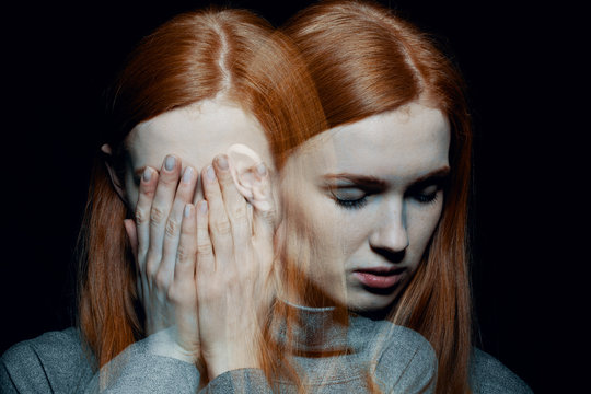 Porter of beautiful redhead girl with psychotic disorders covering her face, hiding from her hallucinations, black background behind her