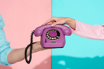 cropped view of man and woman holding purple vintage telephone on pink and blue background