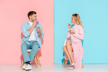smiling couple sitting on chairs, looking at each other and drinking coffee on pink and blue background