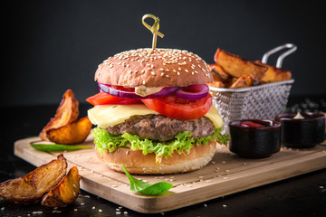 Fresh tasty burger with beef cutlet and fried potatoes on black background