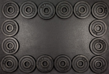 Frame made from black metal weights 1kg on black background with copy sapce.