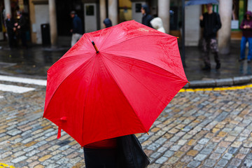 person with red rain umbrella crosses a city street