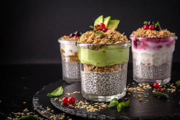 Сhia pudding or yogurt with granola and avocado, mango, wild berries. Healthy breakfast concept and idea. Detox and healthy superfoods.
