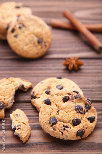 Chocolate Cookies And Cinnamon Sticks On Brown Wooden Background