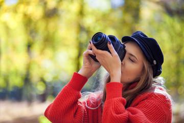 Young woman having fun with camera making photos at green park