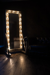 Antique mirror with incandescent lamps and a dark leather sofa