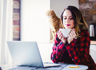 Beautiful young businesswoman have a coffee break while sitting indoors at kitchen. Concept of work with startup business