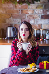 Beautiful young woman sitting and at kitchen with present gifts. Christmas time