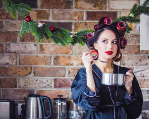 Portrait of young woman in curlers with pan and spoon at kitchen.
